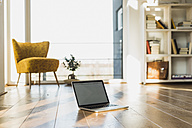 Laptop on wooden floor in an apartment - UUF006417