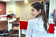 Smiling young businesswoman looking over her shoulder in an office - MGOF001311