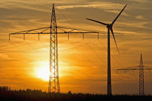Germany, Bavaria, power pylons, wind wheel and evening sun - UMF000796