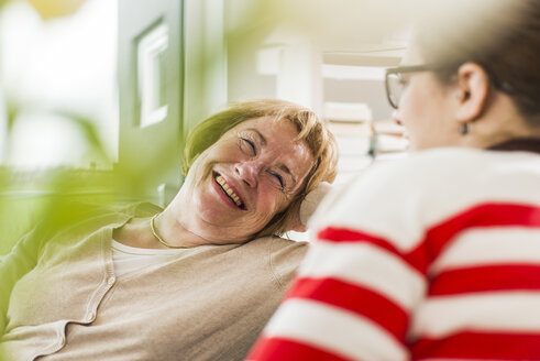 Senior woman smiling at young woman sitting on couch - UUF006443