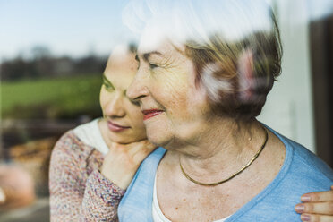 Young woman and senior woman behind windowpane - UUF006455