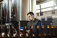 Young man working in craft brewery - ZEDF000043