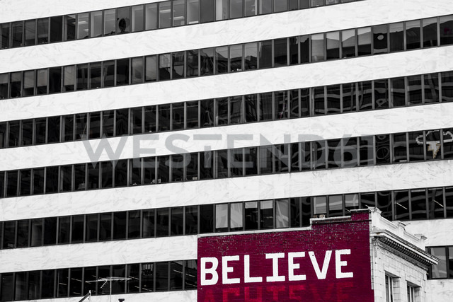 USA, San Francisco, 'Believe' painted on an old residential house in front of a high-rise building - NGF000271 - Nadine Ginzel/Westend61