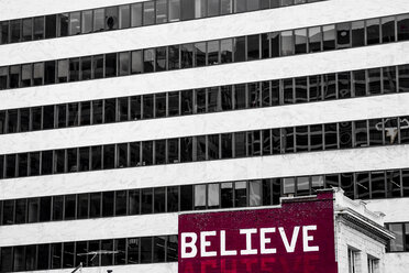 USA, San Francisco, 'Believe' painted on an old residential house in front of a high-rise building - NGF000271