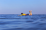 Indonesia, Bali, woman lying on her surfboard floating in the water - KNTF000232
