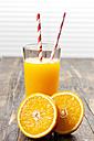 Sliced orange and glass of orange juice on wood - CSF027027