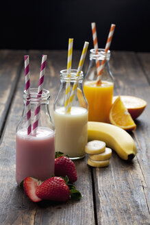 Row of three bottles with different fruit smoothies and orange juice - CSF027036