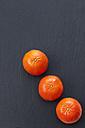 Row of three tangerines on slate - CSF027060