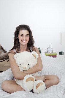 Portrait of smiling young woman with teddy sitting on bed - GDF000960
