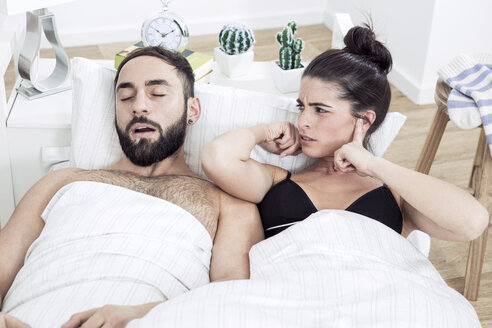 Couple lying in bed with man snoring - GDF000969