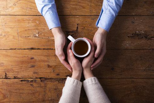 Hands of a young couple holding mug of tea - HAPF000172