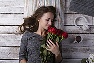 Happy young woman lying on the floor smelling red roses - HAPF000178