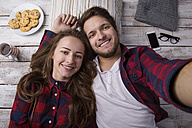 Portrait of young couple lying on the floor taking a selfie - HAPF000184