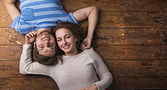Happy young couple in love lying together on wooden floor - HAPF000193