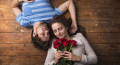 Young couple in love lying on wooden floor - HAPF000196