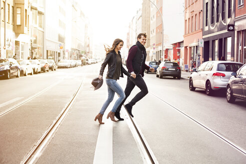 Germany, Berlin, happy couple crossing a street - GCF000127