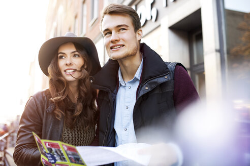 Germany, Berlin, young couple with city map looking around - GCF000136