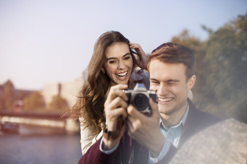 Germany, Berlin, happy young couple with camera at bank of River Spree - GCF000142