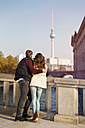 Germany, Berlin, young couple at River Spree looking at TV tower - GCF000151