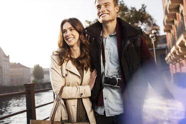 Germany, Berlin, happy young couple walking along River Spree - GCF000157
