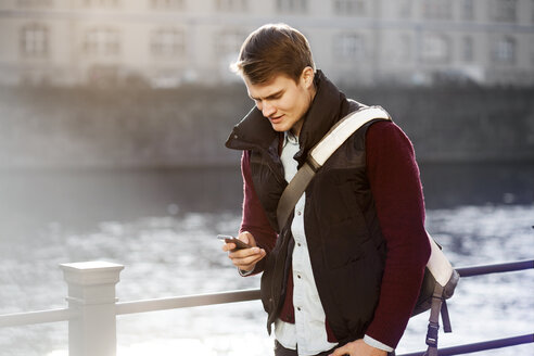 Germany, Berlin, young man holding smartphone at River Spree - GCF000160