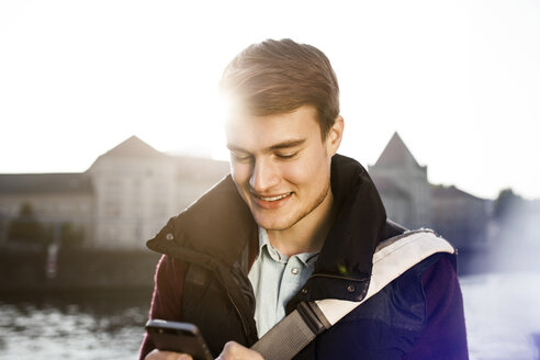 Germany, Berlin, young man holding smartphone at River Spree - GCF000163