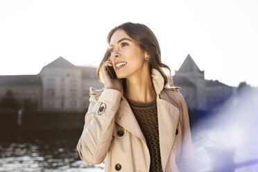 Germany, Berlin, young woman on the phone at River Spree - GCF000166