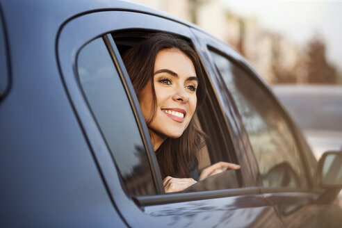 Smiling young woman looking out of car window - GCF000184
