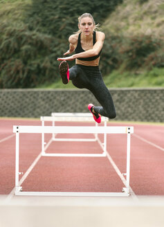 Athlete woman jumping in a running track - MGOF001319