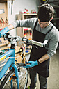 Mechanic repairing a bicycle in his workshop - RAEF000823