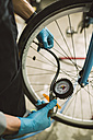 Mechanic adjusting the tire pressure of a bicycle - RAEF000826