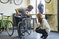 Salesman advising client in a custom-made bicycle store - JUBF000097