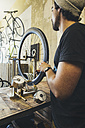 Mechanic working on tire in a custom-made bicycle store - JUBF000106