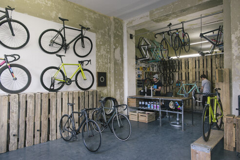 Mechanics working in a custom-made bicycle store - JUBF000109