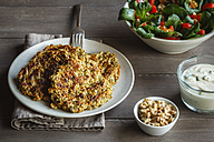 Plate of oat carrot burgers and bowl of mixed salad - EVGF002795