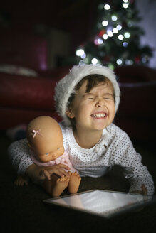 Portrait of little girl wearing Christmas cap with digital tablet and doll at home - MGOF001332