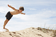 Sweden, Mellby, boy on beach dune jumping into the air with outstretched arms - TSFF000001