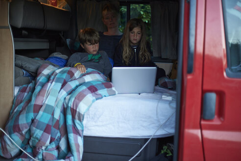 Mother and two children sitting on bed in a camper watching a movie with laptop - TSFF000004