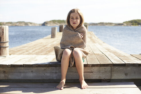 Sweden, Orust, girl sitting on a jetty wrapped in a towel - TSFF000007