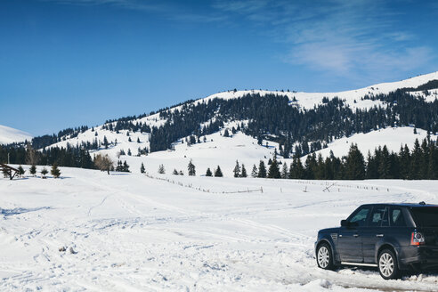 Bulgaria, Pirin mountains, Offroad car during winter in the mountains, snowy field - BZF000277