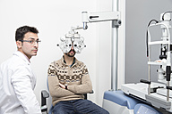Optometrist examining eyesight of a man - ERLF000124