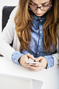 Young woman using her smartphone at desk in the office - AKNF000044