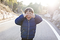 Spain, Siurana, screaming little boy standing on lane of empty country road covering eyes with his hands - VABF000124