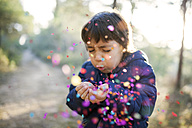 Little boy blowing confetti into the air - VABF000127