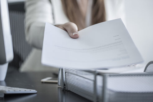 Close-up of woman at desk handing over a document - ZEF008340
