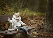 Blond little girl wearing big scarf sitting on a bench in autumn forest - NIF000069