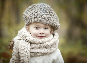 Portrait of happy little girl wearing big scarf and woolly hat in autumn - NIF000072