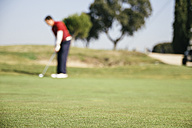Unfocused golfer playing golf on the green of a golf course - ABZF000189