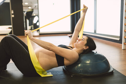 Pregnant woman doing pilates exercises with an elastic band - RAEF000843