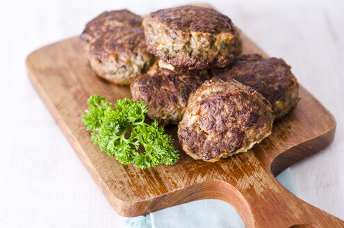 Homemade patties of ground beef with parsley on chopping board - ODF001369